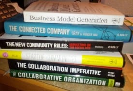 a stack of books such as BUsiness Model Generation and The Connected Company, The New Community Rules and Collaboration Imperative